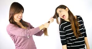 Unhappy girlfriends pulling long hair angry. Beautiful women fighting in studio isolated Stock Image