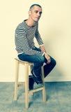 Unhappy gloomy man sitting on stool expressing sorrow. Reflection concept - unhappy 30s man sitting on a stool expressing sorrow, resignation and disappointment Stock Photo