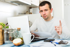 Unhappy guy with notebook at kitchen Stock Image