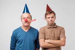 Unhappy guys are on party. Son and father are upset and do not want to have fun.