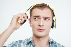 Unhappy handsome young man taking off headphones. Over white background Royalty Free Stock Photos