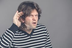 Unhappy hard of hearing man placing hand on ear asking someone to speak up or listening to bad news isolated on gray stock photography