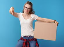 Unhappy hipster with cardboard box showing thumbs down on blue Stock Photo