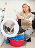 Unhappy  housewife with  clothes near washing machine Royalty Free Stock Photography