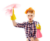 Unhappy housewife holding spray and piece of cloth Royalty Free Stock Images