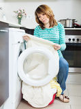 Unhappy  housewife near washing machine Royalty Free Stock Photos