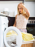 Unhappy housewife near washing machine Royalty Free Stock Image
