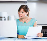 Unhappy housewife reading banking statement Royalty Free Stock Images