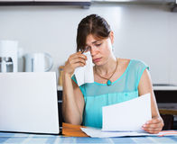 Unhappy housewife reading banking statement Royalty Free Stock Image