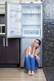 Unhappy and hungry girl near empty fridge Stock Photo
