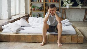 Unhappy husband is sitting on bed after fight with his wife touching his face and lsighing while his wife is lying in