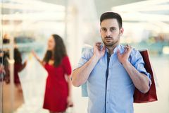 Unhappy husband worried about finances. While shopaholic wife spends money royalty free stock photos