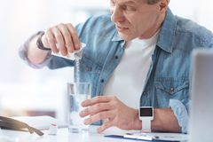 Unhappy ill man preparing his medicine. Sachet with medical powder. Unhappy cheerless ill man holding a sachet and putting its contents into water while Royalty Free Stock Image