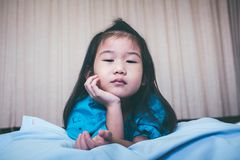 Unhappy illness asian child admitted in hospital. Vintage tone. Illness asian child on sickbed and looking at camera, admitted in hospital. Unhappy girl feeling Stock Photo