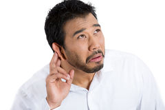 Unhappy irritated man trying hard to hear feeble conversation Royalty Free Stock Photos
