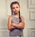 Unhappy kid girl in stylish clothing looking with sad face and f. Olded arms on studio wall background Royalty Free Stock Photo