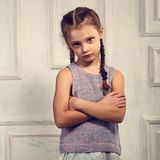 Unhappy kid girl in stylish clothing looking with sad face and f. Olded arms on studio wall background Stock Photography