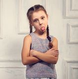 Unhappy kid girl in stylish clothing looking and showing the ton Stock Images