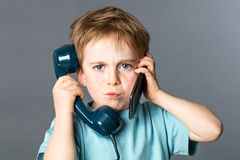 Unhappy kid listening to two voices for burnout communication concept. Unhappy 6-year old red hair kid listening to two voices on an old telephone and a new Royalty Free Stock Photography