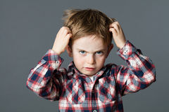 Unhappy kid scratching his hair for head lice or allergies. Mischievous unhappy 6-year old kid with freckles scratching his hair for head lice or allergies, grey royalty free stock image