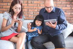 Busy parenting using gadget. Unhappy kid sit in the middle between busy parent using gadget Stock Image