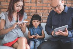 Busy parenting using gadget. Unhappy kid sit in the middle between busy parent using gadget Royalty Free Stock Photos