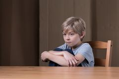 Unhappy kid sitting on chair. Image of unhappy kid sitting on chair hugging legs Royalty Free Stock Photography
