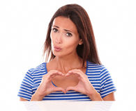 Unhappy lady gesturing a heart sign. Feeling sorry while looking at camera front view in white background Stock Photos