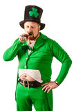 Unhappy Leprechaun smoking a cigar. Photo of a man in a Leprechaun costume smoking a cigar Stock Photography
