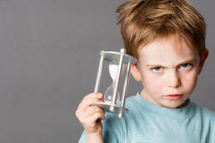 Unhappy little boy with an egg timer for time concept Stock Photo