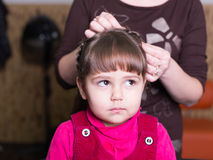 Unhappy little girl at barbershop Stock Image