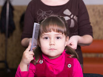 Unhappy little girl at barbershop. Sad little girl at barbershop Royalty Free Stock Images