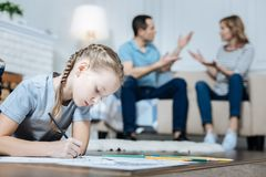 Unhappy little girl drawing on the floor. Drawing. Unsmiling blue-eyed little girl drawing and lying on the floor while her parents shouting at each other Royalty Free Stock Image