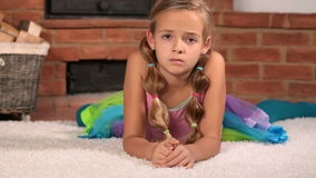 Unhappy little girl on the floor. Unhappy little girl lying disappointed on the floor stock footage