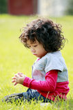 Unhappy little girl on the grass Stock Photo