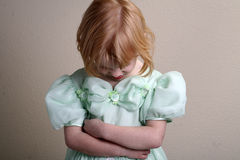 Unhappy Little girl green dress. A little girl in a green dress who is not very happy Royalty Free Stock Images