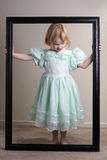 Unhappy Little girl green dress framed. A little girl in a green dress who is not very happy inside her black frame Royalty Free Stock Images