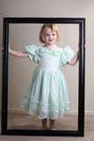Unhappy Little girl green dress framed Stock Photos