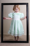 Unhappy Little girl green dress framed. A little girl in a green dress who is not very happy inside her black frame Royalty Free Stock Photography