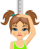 Unhappy little girl measuring her growth in height Stock Photography