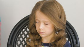 Unhappy little girl. Mom or barber braids her braids. Brown hair stock video