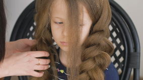 Unhappy little girl. Mom or barber braids her braids. Brown hair stock video footage