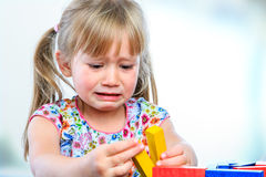 Unhappy little girl playing with wooden blocks. Close up portrait of crying little girl playing with wooden blocks at table.Frustrated girl showing moody Royalty Free Stock Image