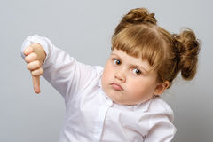 Unhappy little girl showing thumb down. Gesture isolated Stock Images