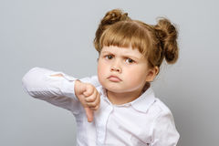 Unhappy little girl showing thumb down. Gesture isolated Stock Photography