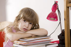 Unhappy little girl sitting at the desk Royalty Free Stock Photos