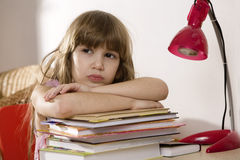 Unhappy little girl sitting at the desk. Unhappy little girl studying at the desk Stock Images