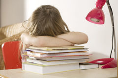 Unhappy little girl sitting at the desk Stock Images