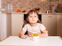 Unhappy little girl with spoon and cake Royalty Free Stock Photos