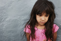 Unhappy little girl standing against grey wall. Close up portrait of unhappy little girl standing against grey wall with copy space. Young girl looking upset Royalty Free Stock Image